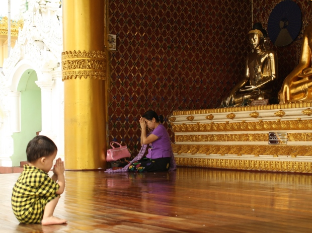 A little boy squats into prayer position below four golden Buddhas.