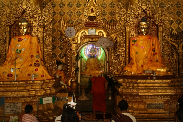 A large meditation room. The monk in front is  about to kneel down in front of the LED lit Buddha in the center.