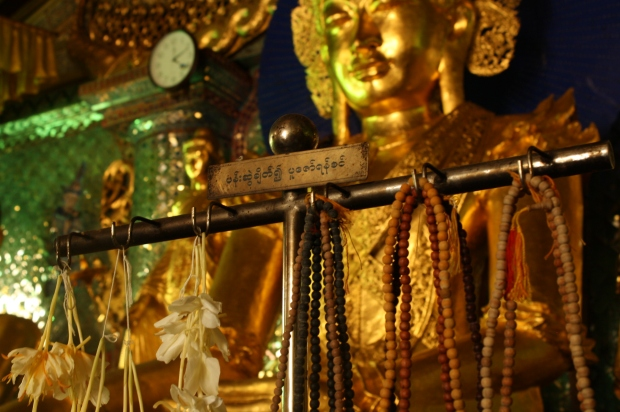 Mala beads and flowers hang in front of many statues.
