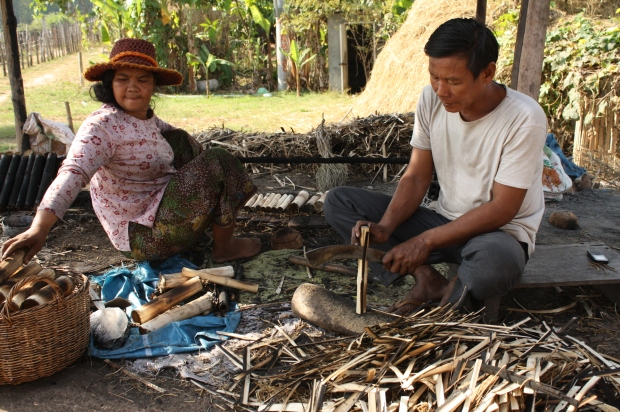 This couple is making sticky rice by the dozens. She takes the stuffed bamboo and places it over the coals, rotating through batches. Once a batch is done cooking, he takes each one and shaves the burnt sides so you can peel the bamboo back more easily.